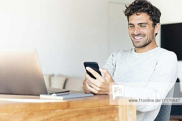 Smiling man with laptop using mobile phone while sitting by table at home
