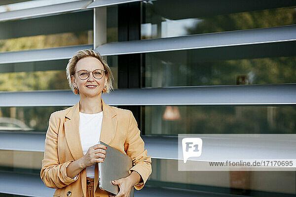 Confident mature businesswoman with laptop against office building