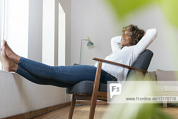 Thoughtful woman with hands behind head relaxing on armchair at home