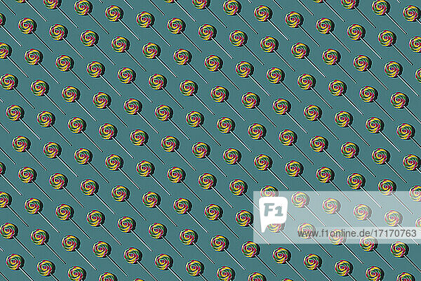 Pattern of multi colored lollipops against green background