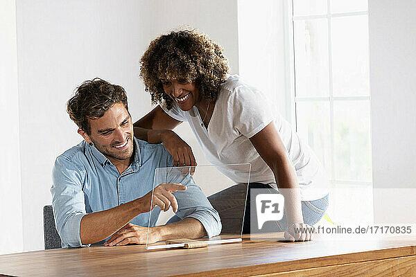 Lächelndes Paar berührt den Bildschirm eines transparenten Geräts  während es zu Hause sitzt