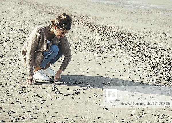 Junge Frau zeichnet Herz auf Sand am Strand Junge Frau zeichnet Herz auf Sand am Strand