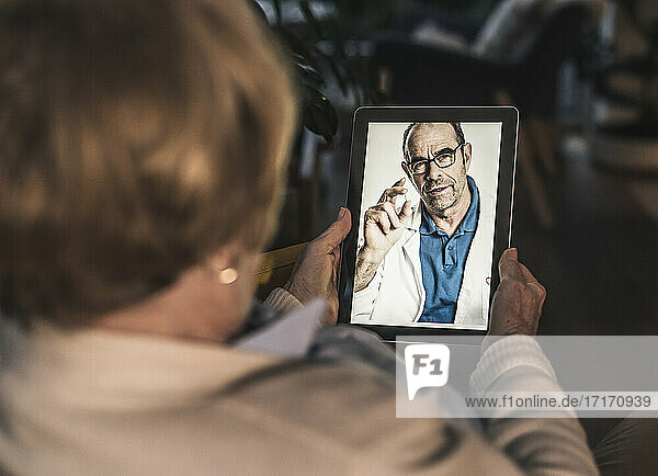 Mature male doctor showing medicine to senior patient on video call at home