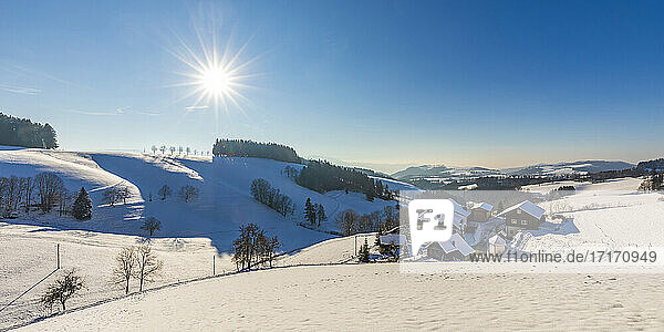 Germany  Baden-Wurttemberg  Sankt Margen  Sun shining over houses of town in middle of Black Forest in winter