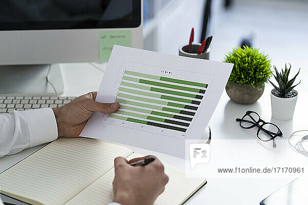 Businessman with graph paper document working on desk at work place