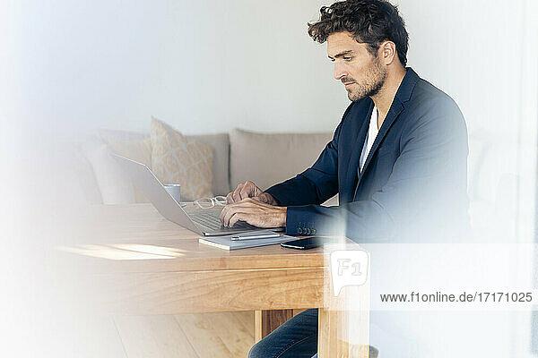 Geschäftsmann  der einen Laptop benutzt  während er zu Hause sitzt Geschäftsmann, der einen Laptop benutzt, während er zu Hause sitzt