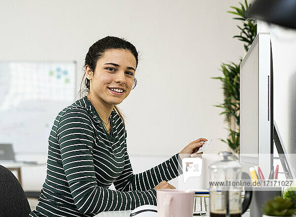Creative businesswoman holding credit card while sitting by computer in office