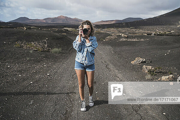 Young tourist standing with camera on footpath at Volcano El Cuervo  Lanzarote  Spain
