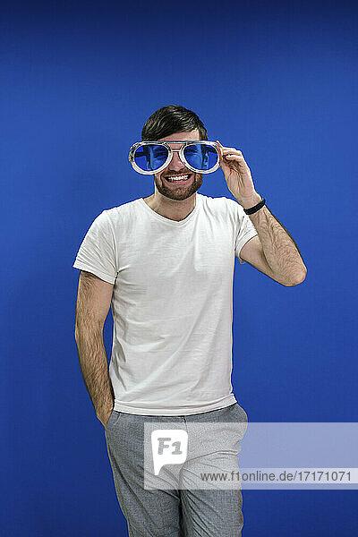 Fröhlicher Geschäftsmann mit Händen in den Taschen und übergroßer Sonnenbrille vor blauer Wand im Büro Fröhlicher Geschäftsmann mit Händen in den Taschen und übergroßer Sonnenbrille vor blauer Wand im Büro