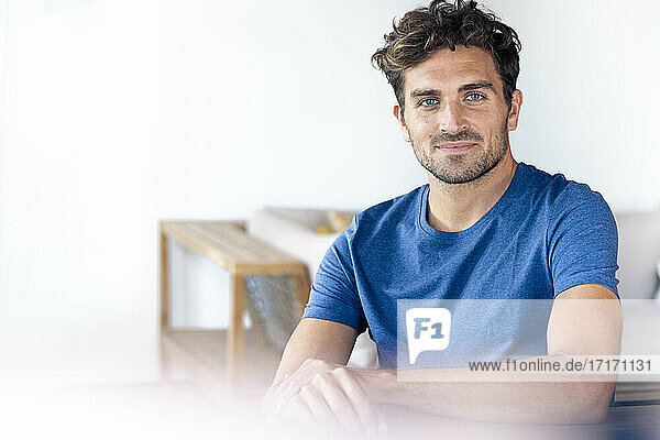 Handsome man with blue eyes smiling while sitting at home