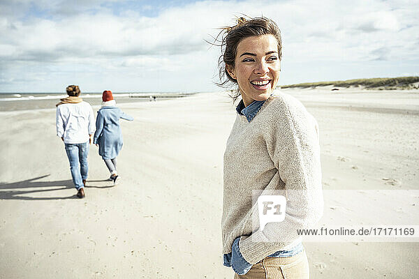 Portrait of young woman walking on sandy beach with two people in background