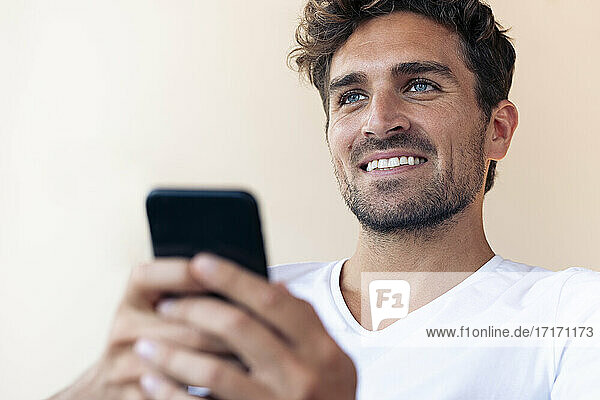 Gut aussehender Mann  der lächelt  während er sein Smartphone zu Hause benutzt Gut aussehender Mann, der lächelt, während er sein Smartphone zu Hause benutzt