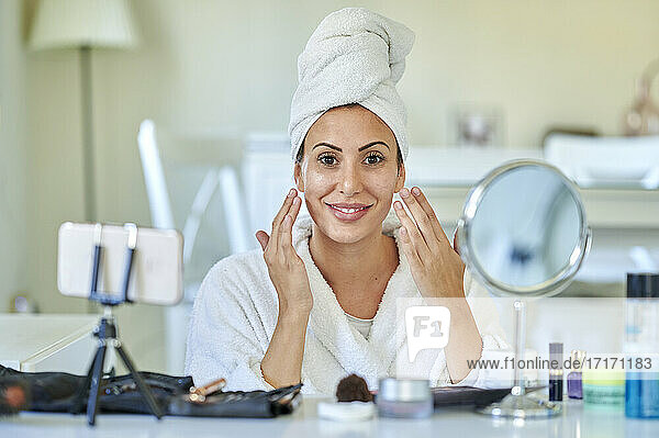 Female blogger applying face cream on her face while vlogging on smart phone at home