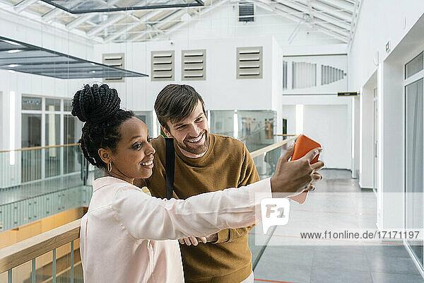 Lächelnde multiethnische männliche und weibliche Kollegen machen ein Selfie mit ihrem Smartphone am Arbeitsplatz Lächelnde multiethnische männliche und weibliche Kollegen machen ein Selfie mit ihrem Smartphone am Arbeitsplatz