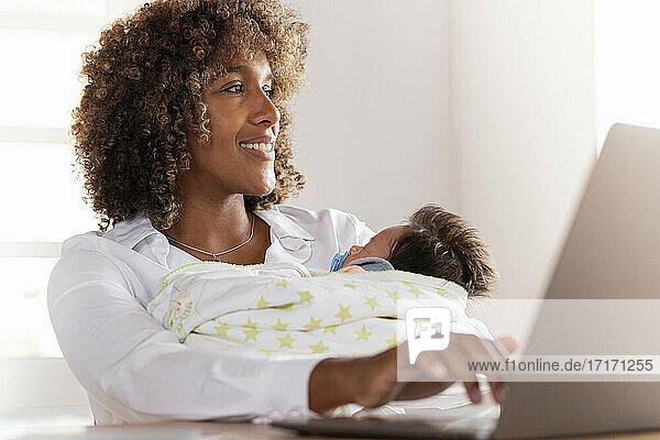 Lächelnde Frau,  die am Laptop arbeitet,  während sie mit ihrem Baby im Home Office sitzt