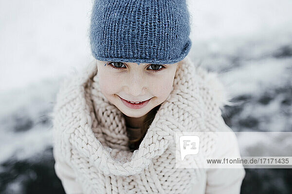 Happy small girl in warm clothing during winter