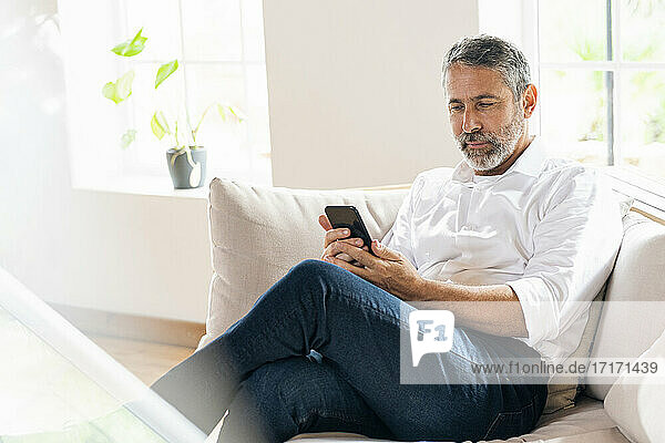 Businessman using mobile phone while sitting on sofa at home