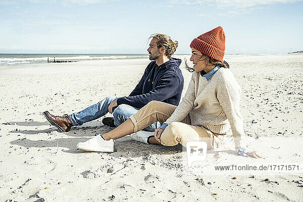 Young couple sitting together on beach sand