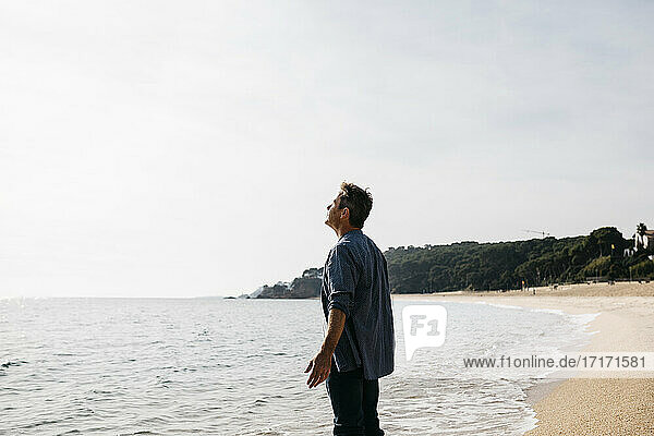 Man with arms outstretched enjoying at beach during sunny day