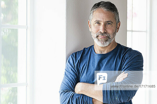 Confident businessman standing with arms crossed at home