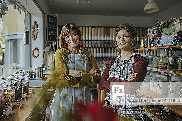 Smiling female saleswoman and owner with arms crossed at zero waste store