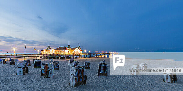 Germany  Mecklenburg-Western Pomerania  Heringsdorf  Hooded beach chairs on empty beach at dusk with illuminated Ahlbeck Pier in background