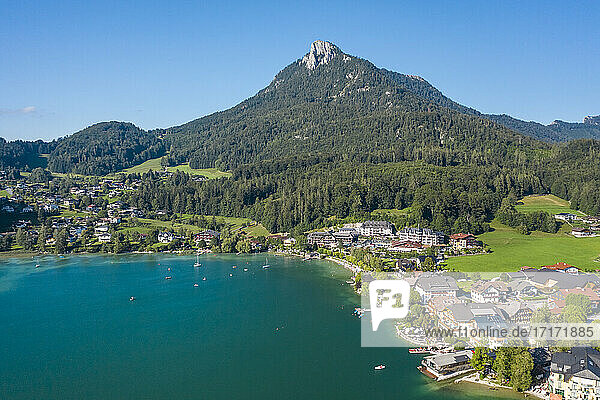 Austria  Salzburg  Fuschl am See  Aerial view of town on shore of Lake Fuschl in summer with forested mountain in background