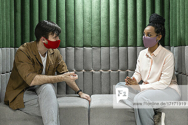 Businesswoman discussing with male colleague while sitting on sofa during pandemic in office