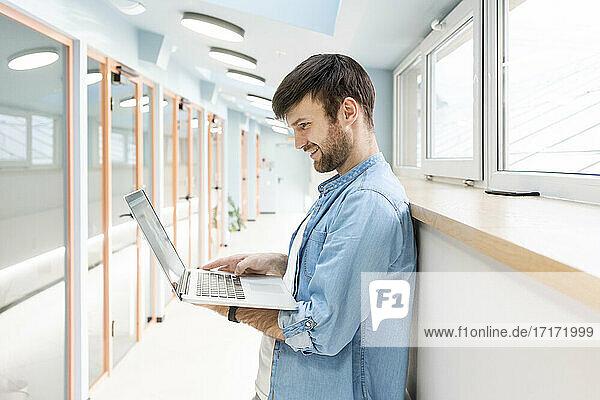 Lächelnder kreativer Geschäftsmann  der einen Laptop benutzt  während er im Bürokorridor steht Lächelnder kreativer Geschäftsmann, der einen Laptop benutzt, während er im Bürokorridor steht