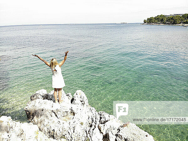 Woman with arms raised looking at sea while standing on rock during sunny day