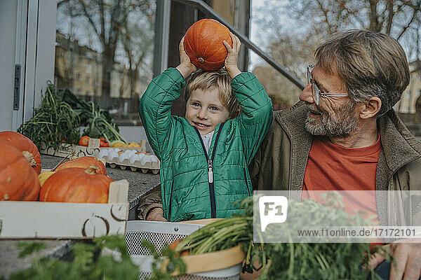 Smiling father looking at playful son holding pumpkin while shopping at shop