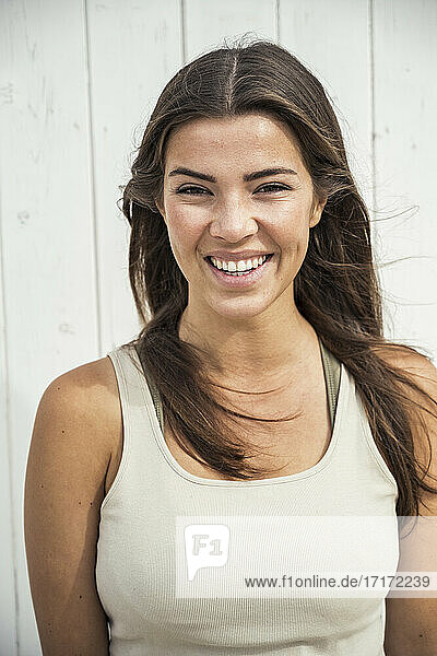 Happy young woman in tank top against beach hut