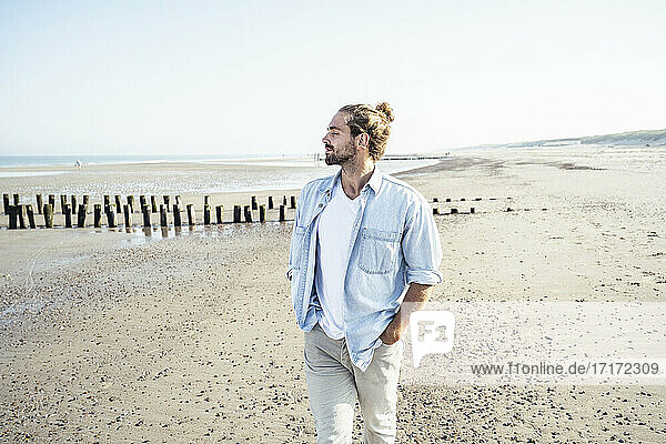 Handsome man with hands in pockets standing at beach on sunny day