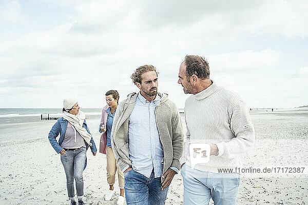 Two men walking and talking side by side along sandy beach