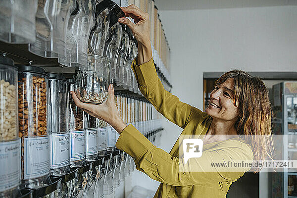 Smiling mature customer using food dispenser at retail store