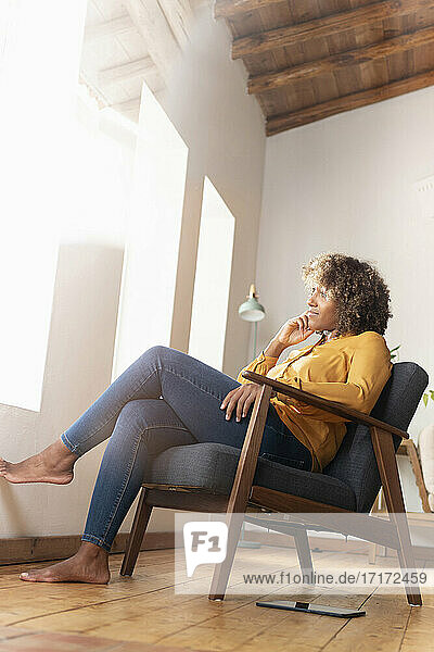 Thoughtful woman with hand on chin looking away while sitting on armchair at home