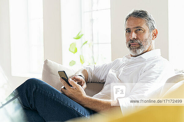 Businessman with smart phone looking away while sitting at home