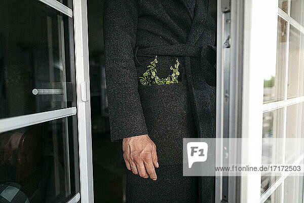 Mature man in black coat with plant in pocket standing at doorway