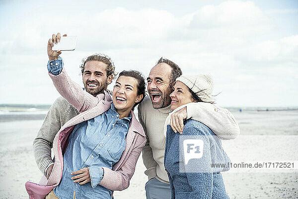 Group of friends taking selfie at beach
