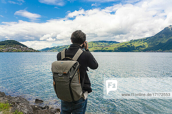 Male tourist with backpack photographing Sarner lake against cloudy sky in Switzerland