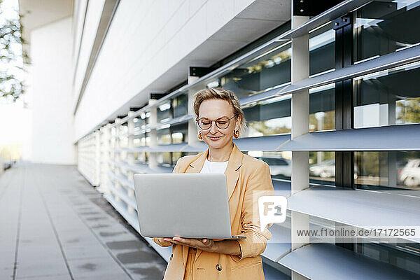 Female entrepreneur using laptop while standing against office building