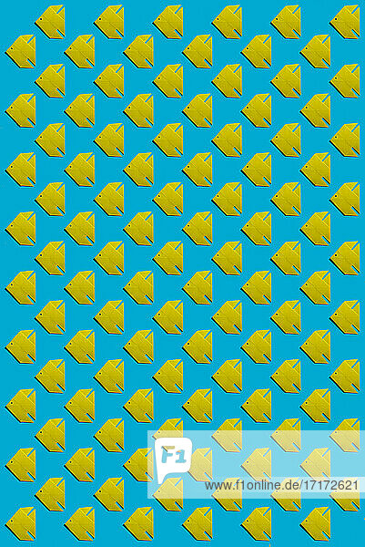 Pattern of yellow origami fish against blue background