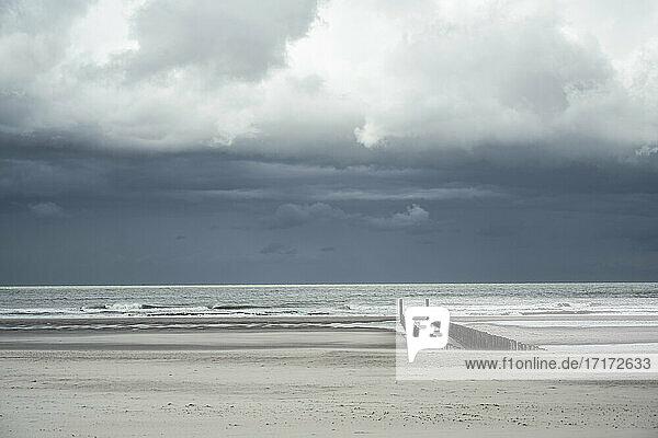 Sturmwolken über leerem Küstenstrand Sturmwolken über leerem Küstenstrand