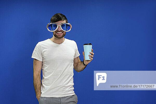 Lächelnder Geschäftsmann mit einer neuartigen Brille  der einen wiederverwendbaren Kaffeebecher vor einer blauen Wand im Büro hält Lächelnder Geschäftsmann mit einer neuartigen Brille, der einen wiederverwendbaren Kaffeebecher vor einer blauen Wand im Büro hält