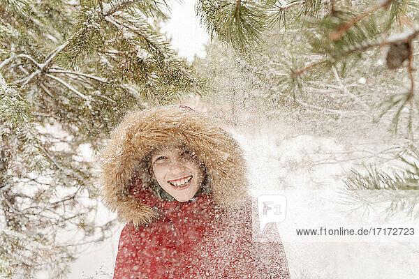 Cheerful boy enjoying snowfall in forest
