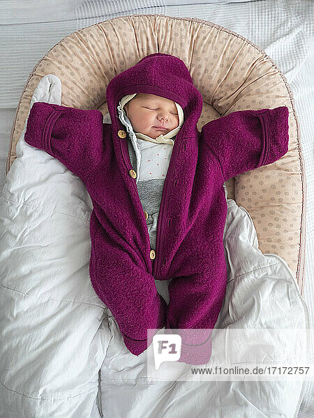Cute baby girl in warm clothing sleeping on bed at home Cute baby girl in warm clothing sleeping on bed at home
