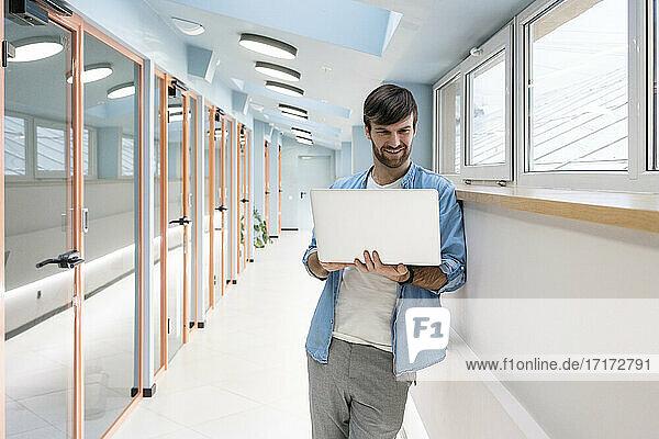Kreativer männlicher Unternehmer  der an einem Laptop arbeitet  während er sich an die Wand im Korridor lehnt Kreativer männlicher Unternehmer, der an einem Laptop arbeitet, während er sich an die Wand im Korridor lehnt