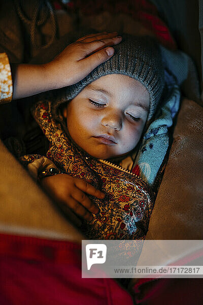 Sister admiring baby girl with warm clothing while sleeping during winter