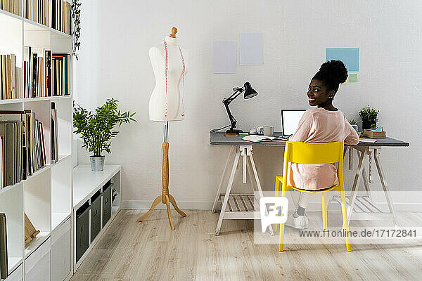 Businesswoman smiling while sitting by mannequin at home office