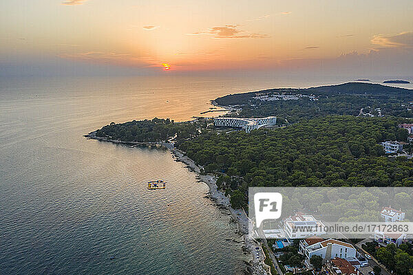 Croatia  Istria County  Rovinj  Aerial view of forested shore of coastal city at summer sunset
